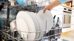 close-up of female hands loading dishes to the dishwasher; adult; blue; casual; caucasian; cleaning; close-up; clothing; dishes; dishware; dishwasher; domestic; everyday; female; hand; holding; home; housecleaning; housework; human; hygiene; indoors; inserting; interior; kitchen; life; one; part; people; person; plate; routine; scenes; washing; women; young